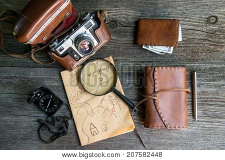 Personal travelers accessories: camera, notebook, purse, compass, magnifier, pen, money, map. Vintage background.