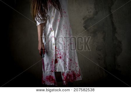 Closeup Ghost woman holding knife for kill with blood violence in house of ruin nightmare horror of scary fear on hell is monster devil in halloween festival copy space the right.