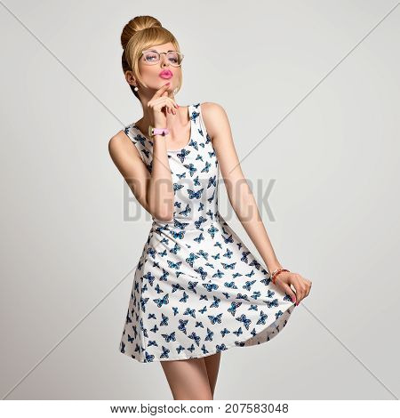 Fashion Young Blond Woman in Stylish glasses, Summer Outfit. Stylish Trendy Pinup hairstyle, fashion Glamour Makeup, Blue Eyes. Pretty Model Girl in Butterfly summer Dress. Beautiful pinup lady