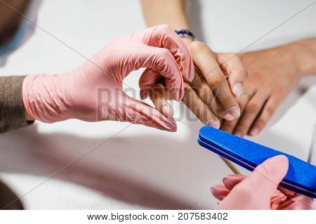 Woman getting nail manicure in salon. Care for hands. manicure master makes the nails smooth using the nail file with smooth ends purple