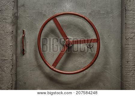Closed hermetic door with red handweel of old soviet bunker