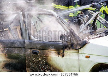 Fireman and burning car after crash. detail