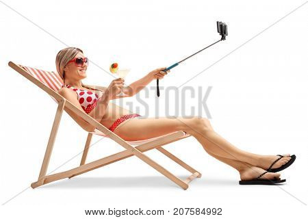 Young woman sitting in a deck chair and taking a selfie with a stick isolated on white background