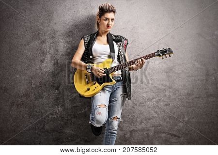 Female punker playing an electric guitar and leaning against a rusty gray wall