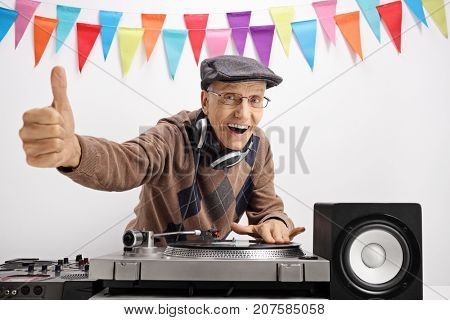 Senior playing music on a turntable and making a thumb up sign against a wall with decoration flags