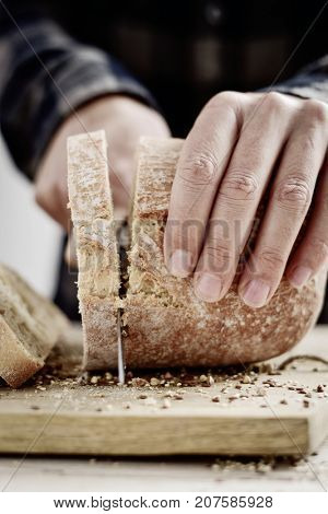 closeup of a young caucasian man cutting a spelt bread roll in slices with a knife