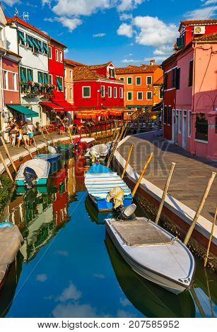 Burano island in Venice Italy picturesque over canal with boats among old colourful houses stone streets.