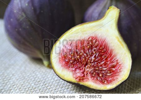 Fresh ripe fig fruits on a burlap cloth background.Whole and sliced figs close up.Tasty organic figs.Selective focus.