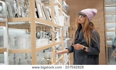 A young hipster female in fashion glasses chooses home acessories in the store. Shopping