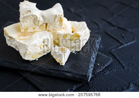 Delicious traditional Italian festive torrone or nougat with nuts on black stone background. Soft nougat blocks with almonds. Holiday concept. Italian sweets.