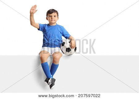 Small boy with a football sitting on a panel and waving isolated on white background
