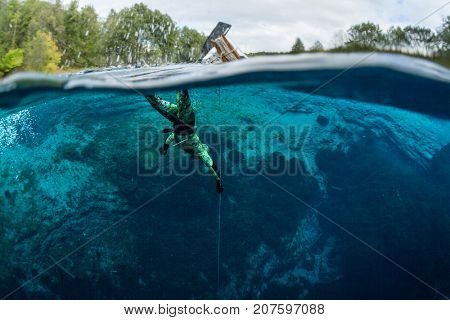 Split shot of a man diving in a blue crystal clear lake