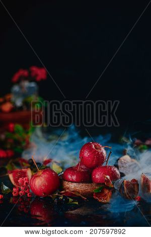 Tiny Red Apples On A Wooden Plate In An Autumn Still Life With Leaves And Smoke.