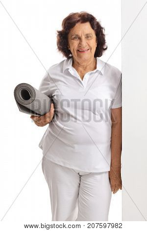 Elderly woman with an exercise mat leaning against a wall isolated on white background