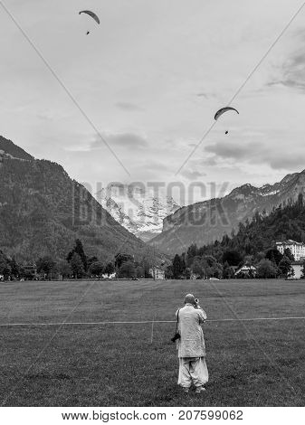 Interlaken Switzerland - May 26 2016: Paragliders flights over the Swiss Alps and photographer in the foreground in Interlaken Switzerland. Black and white photography.