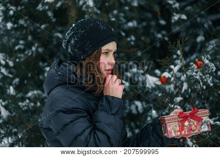 girl found a gift under tree and represents what is inside the box. A child with a gift. New Year. A box with a gift for Christmas.