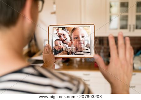Unrecognizable young father at home holding a tablet, video chatting with wife and children.