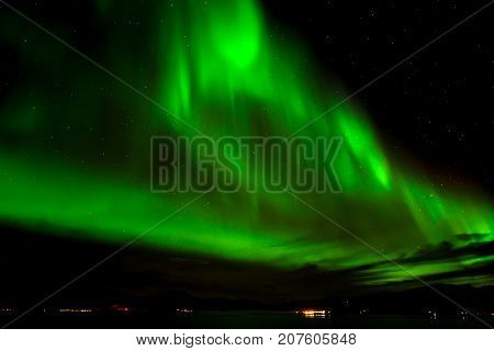 A beautiful green Aurora borealis or northern lights in the sky at Tromso Norway
