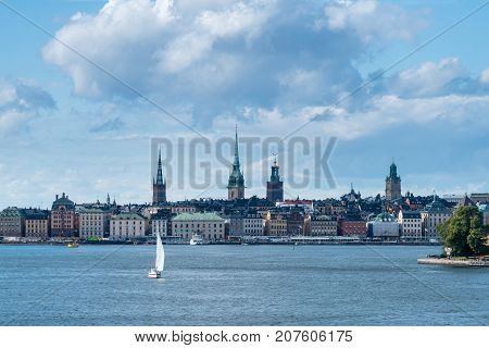 Panorama of Gamla Stan in Stockholm, Sweden with a yacht leaving the harbor