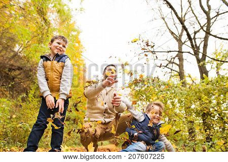 Young father with his sons on a walk outside in colorful autumn forest, throwing leaves in the air.
