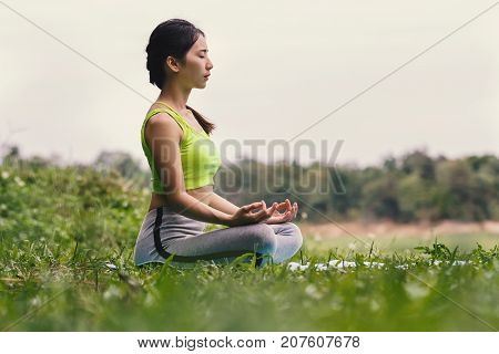 Young asian woman in sportswear meditating on yoga mat vintage tone