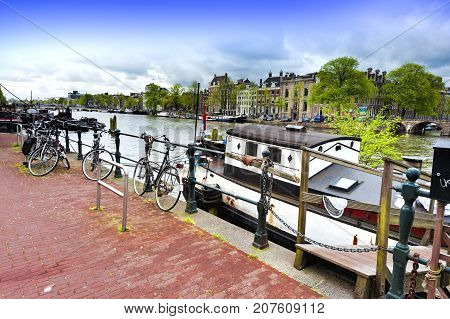 Urban scene in Amsterdam with houseboat and many bicycles. Street View with bikes parked on an embankment in the historical center of Amsterdam in the Netherlands