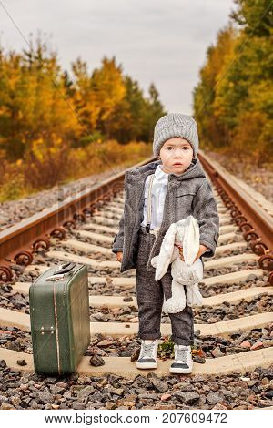 a lost little boy in vintage clothes hugs a bunny next to an old-fashioned suitcase in the middle of the forest on an abandoned railway rails