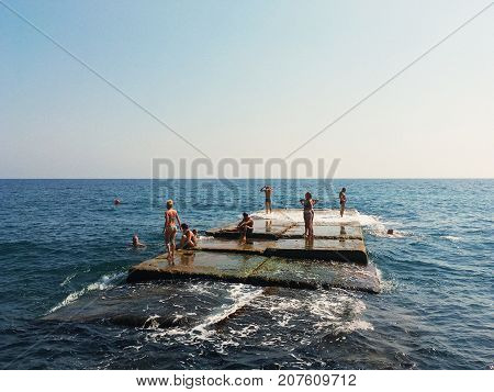 Yalta Crimea - September 20 2017: group of people swimming and sunbathing on breakwater