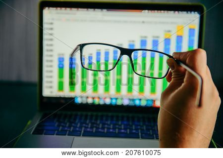 hand holds glasses in front of laptop with diagram on it concept