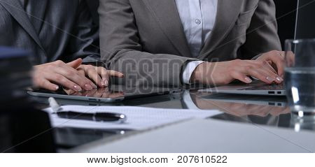 Group of businesspeople or lawyers at meeting. Close-uo of human hands at work. Low key lighting. poster