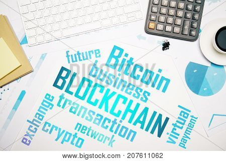 Top view of white office desktop with blockchain text. Bitcoin cocnept