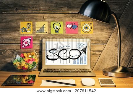 Creative designer desktop with table lamp SEO sketch on laptop scree various devices and stickers with rocket icons on wooden wall. SEO and finance concept