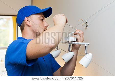 electrician at work - installing lamp on the wall