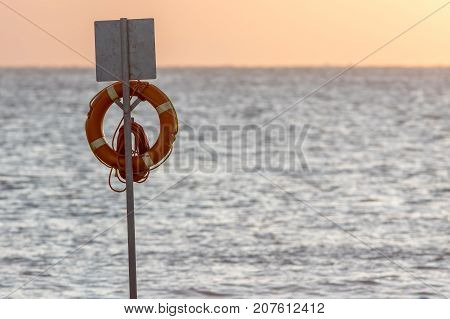 Lifesaver flotation ring. Beach lifebuoy ring on stand in front of sea. Lifeguard emergency equipment image with copy space.