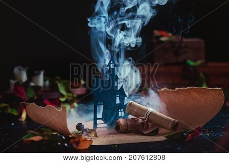 Haunted Castle In Clouds Of Smoke On A Magical Scroll. Conceptual Halloween Still Life With Smoke, W