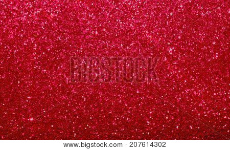 Brilliant red shimmer and glitter background.  Holiday or romance, shine and texture backdrop.  Christmas, Valentine's Day or wedding theme.
