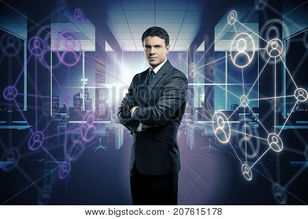 Handsome young businessman with folded arms standing in blurry office interior with glowing HR holograms. Interface concept. Double exposure