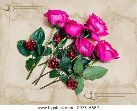 Beautiful pink roses with gift bows on beige background. Vintage style
