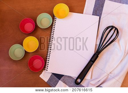 Whisk cupcake silicon baking cups and empty notebook on wooden background