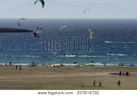 Sandy beach and the kitesurfers on the waves of the Aegean sea at Prasonisi (Greece)