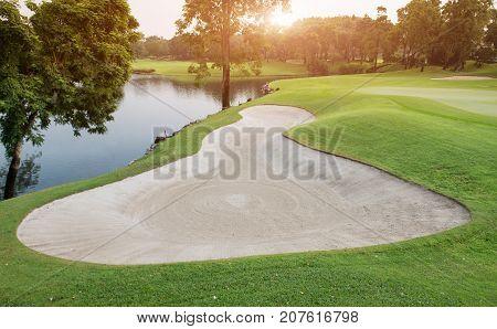 Sand Bunker In Green Golf Fairway.