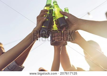 Group of young friends having fun at rooftop party drinking beer making a toast and enjoying hot summer days. Selective focus on the beer bottles