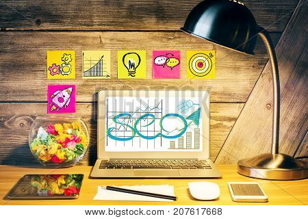 Creative designer desktop with table lamp SEO sketch on laptop scree various devices and stickers with rocket icons on wooden wall. SEO and media concept
