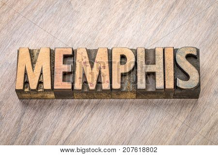 Memphis word abstract in vintage  letterpress wood type against grained wooden background