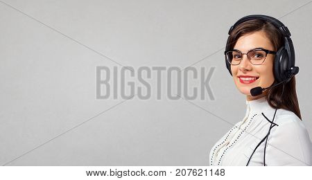 Young woman call center operator in headset on gray background.