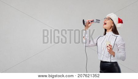 A woman in a Santa Claus hat sings a karaoke into the microphone on a gray background.