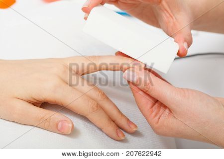 Nail care beauty wellness spa treatment concept. Woman preparing nails before manicure beautician file nails