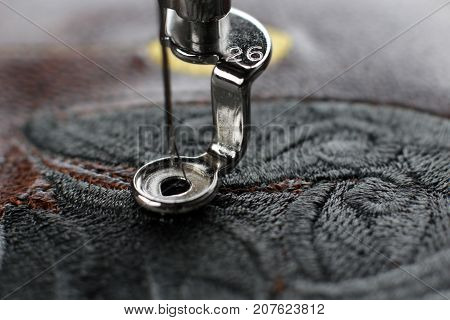Multilayer embroidery on brown leatherette with embroidery machine - close up