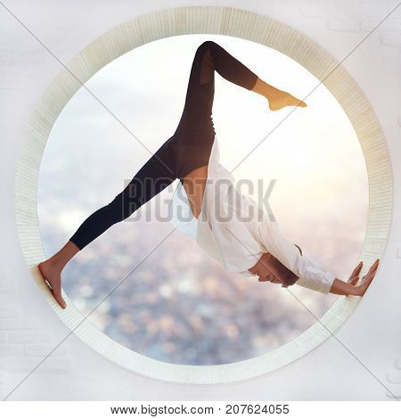 Beautiful sporty fit yogi woman practices yoga asana eka pada Adho Mukha Shvanasana One Leg Downward Dog pose in a round window with a view of the city at sunset.
