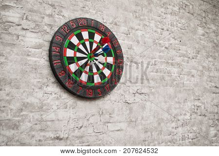 The Darts stick to the target, the Darts on the gray brick wall
